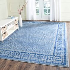 Add an understated touch of color to your dining room or den with this stately area rug, featuring a classic diamond motif and vibrant blue border.