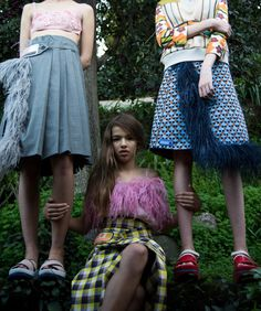 Left to right: PRADA beaded bra top and pleated wrap skirt with patches and feather side and BOSS slides. PRADA silk and feather top and wrap skirt with patches. PRADA leather vest, button-down shirt, wrap skirt with patches and feather side, shoes, and belt.