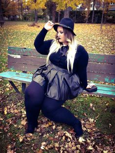 plus size goth witchy outfit with leather skirt, black top, and fedora
