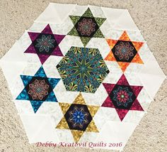 "Circle of 6 stars with an interfaced larger kaleidoscope hexagon in the center. Block finishes to 7"" high."