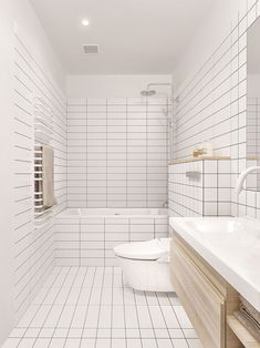 The floor of this bathroom is covered in clean white rectangular tiles mixed with a single line of square tiles to add a touch of interest.