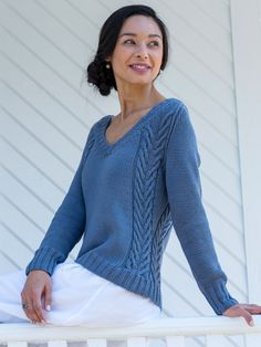 Paired traveling cables at the sides create a flattering silhouette for this raglan v-neck sweater knitting pattern. Cable patterns are charted.