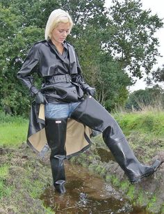 Black rubber raincoat and hip waders in the mud