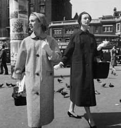 Two models wearing loose fitting button front coats for Vanity Fair, June 1956.