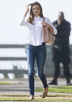 Ready to go: Seen here arriving to the shoot in a crisp white shirt and blue jeans...