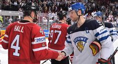 MAY 17: Finland's Mikko Koivu #9 shakes hands with Canada's Taylor Hall #4 during preliminary round action at the 2016 IIHF Ice Hockey World Championship.