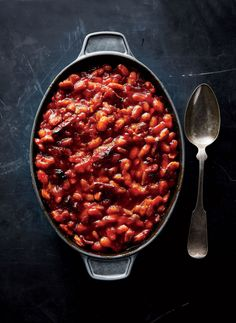 Maple-Bacon Baked Beans | Think of this dish as classic baked beans turned all the way up to 11--sweet, smoky, and saucy, with extra richness from the slow-simmered beans. The starchiness from the cooked beans will help bind the casserole. Curry powder adds a hint of earthiness, but you can leave it out for a more straightforward flavor.
