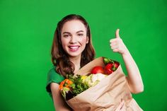 Young smiling woman with a paper bag of vegetables. on green