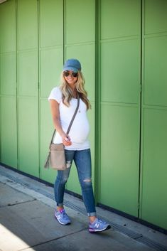 Casual maternity look with a simple tee, cuffed jeans, baseball hat, and sneakers.