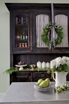 Add splashes of green and white to bring the holiday spirit into the heart of the home. Details can be as simple as a wreath hung with striped ribbon and seasonal greenery or sparkly ornaments strewn on surfaces.