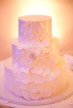 Brides: White Wedding Cake with Oversize Flower. A three-tiered white wedding cake with sugar flower details, created by Belle Mer.