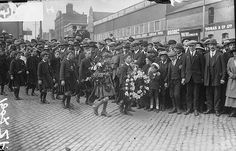 Michael Collins' Funeral. These boys dressed in Na Fianna Éireann uniforms are carrying wreaths as part of the funeral procession of Michael Collins. 28 August 1922, National Library of Ireland