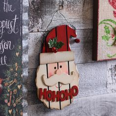 "Make your holidays a little brighter with Kirkland's Distressed Wood Plank Santa Plaque! His hat features a holly and jingle bell accent and the plaque reads ""Ho Ho Ho."""