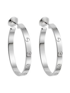 "A timeless pair of Cartier ""Love"" earrings featuring the iconic screw motifs in 18k white gold."