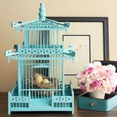 Decorative touches like this turquoise-painted oriental birdcage can become focal points in an Asian-inspired room. Birdcage vignette photo from Better Homes and Gardens.