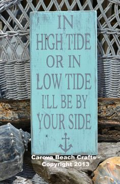"This hand painted, sea glass green hanging sign or shelf sitter reads, ""In High Tide Or Low Tide I'll Be By Your Side"" with an anchor. in painted gray lettering and measures approx 20"" H x 10""W. A saw"