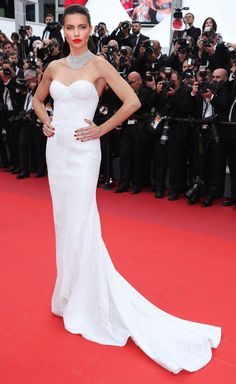 2017 Cannes: Adriana Lima is wearing a white strapless Naeem Khan dress. Stunning and gorgeous! This gown fits him perfectly and the white pops really well agains her tan skin. I love the necklace!