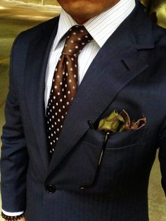 Shop this look for $219: http://lookastic.com/men/looks/brown-tie-and-white-dress-shirt-and-olive-pocket-square-and-navy-blazer/1513 — Brown Polka Dot Silk Tie — White Vertical Striped Dress Shirt — Olive Print Silk Pocket Square — Navy Blazer