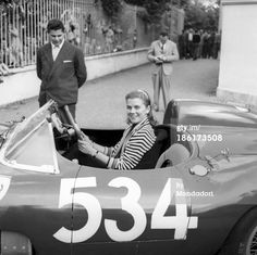 Louise Collins posing smiling at the wheel of the car driven by her husband and British racing driver Peter Collins at the Mille Miglia Automobile Race. Italy, May 1957. (Photo by Emilio Ronchini/Mondadori Portfolio via Getty Images)