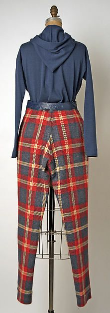 Bonnie Cashin: Day ensemble 1967. Bonnie Cashin (American, 1915–2000). Natural cotton, red–and–blue plaid wool, and navy blue wool jersey. This day ensemble equalizes men and women without surrendering to menswear design. The conical shape of the swing jacket in canvas is definitely womenswear, though its special ingenuity resides in Cashin's eminently practical dog-leash latching, whereas the plaid trousers could easily come from the menswear wardrobe of a misguided golfer.