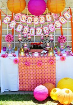 """Set up the luncheon space with pretty paper lanterns, strings of fake flowers, and some sort of banner that reads """"Happy Mother's Day"""". If you have an accent color, make sure you associate that accent color with the decorations! Here's a nice example of a mother's day set up that could inspire your own!"""