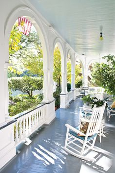 Charming Southern front porch with arches, blue ceiling, and white rocking chairs. #frontporch #decoratingideas #blueceiling