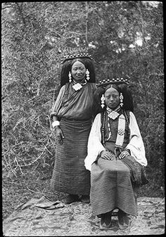 Photographer: LtCol R. S. Kennedy?, WilloughbyPatrick Rosemeyer?, Collection: Sir Charles Bell, Date of Photo: 1920-1921 or 1922, Region: Lhasa High status Tibetan woman, seated, with a female servant, standing. The women are distinguished by their clothing and clothing accessories. They have been photographed outside, against a backdrop of trees, with the seated woman sitting on a chair on a carpet.