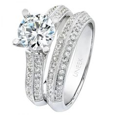 This dazzling 18k white gold diamond engagement ring with matching band from the Bouquet Collection features micro-pave set diamonds and milgrain accents. Handcrafted and designed by Uneek Fine Jewelry.