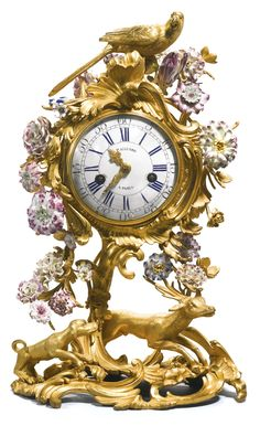 A Louis XV porcelain mounted gilt-bronze mantel clock, circa 1750 5-inch enamel dial signed Paillard A Paris with blue Roman numerals, similarly signed bell striking movement No.702 with flat bottomed plates, silk suspension and outside numbered countwheel, the drum case within a bocage of colourful porcelain flowers, the leaf and 'C' scroll base with a hound coursing a stag, the whole surmounted by a parrot,