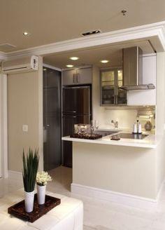 A pequena cozinha americana é completa com fogão cooktop, coifa, geladeira e armários
