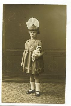 A girl wearing a big, perky hair bow and holding a little doll | Flickr - Photo Sharing!
