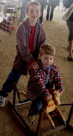 Small fry shopper Cecil Hunt, 8 helps his brother Quinn, 4, ride a 1950s Davy Crocket horse offered by dealer Tom Svast of Griffith, Ind. The lads, from Taylorville, Ill., were chaperoned at the market by their father Brandon Hunt.