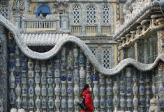"""A woman walks in front of the """"China House"""" in Tianjin on January 5, 2008. The house is decorated with hundreds of millions of ancient porcelain flakes, ancient bowls, dishes and vases, inlaid everywhere in the architecture."""