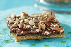 Graham crackers baked with a topping of melted butter and brown sugar are covered with chocolate and pecans then broken into pieces of candy brittle.
