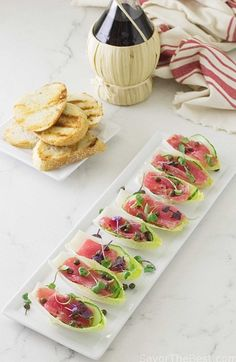 Tuna Crudo appetizers are delicate slices of raw tuna, drizzled with a light lemon vinaigrette and served with cucumber slices in Belgian endive boats.