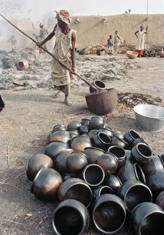 Africa | Sights and Sounds.  Mali.  Women firing newly-made pottery in the village of Kalabougou