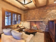 The stone wall is wonderful with the STUCCO walls and beams on the ceiling. This coffee table is super too.
