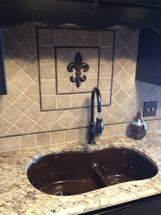 Fleur de lis backsplash - I got the fdl from Hobby Lobby and painted it to match the bronze pieces from Lowes that I was using for my backsplash.