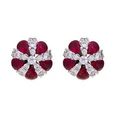 A pair of ruby and diamond cluster earrings, five pear cut rubies, combined weight of 2.60cts alternating with round brilliant cut diamonds all radiating from a brilliant cut diamond centre, total weight of 0.97ct, mounted in an 18ct white gold setting with post and scroll fittings.