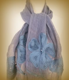 Smokey blue large linen scarf with silky flat ribbon rosettes and freshwater pearls. Beautiful, natural and soft with a lovely open weave. This lovely smokey blue scarf is appliqued with a sliky flat ribbon swirled around to create a lovely organic flower design highlighted with a blue frehswater pearl. $50.00