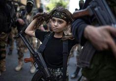 Esta niña palestina lleva entre sus brazos un rifle Kalashnikov. Esta imagen la tomó Wissam Nassar para el New York Times.  - See more at: http://culturacolectiva.com/la-condicion-humana-en-30-fotografias/#sthash.7bzkGxhz.dpuf