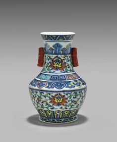 Small Chinese wucai enameled porcelain vase; of baluster form with angled shoulder, two bamboo-motif, coral red and gilt tubular handles; the body decorated with lotus blossoms amid scrolling foliage; Qianlong mark but later, possibly 19th Century; H: 7 3/4""