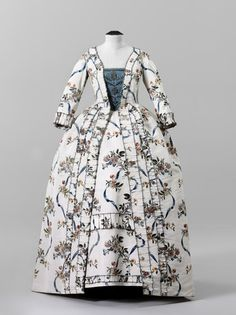 Robe à la francaise, c. 1775. White silk, painted with a design of floral sprays and blue ribbon, self-fabric trimming.