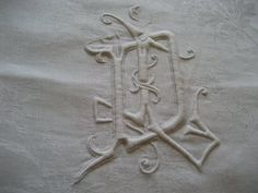 Interlaced monogram LD or DL, superb detail, on a fine linen damask tablecloth sold by chatelaine-chic.