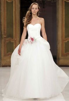 Strapless long white wedding dress with full skirt, pink flower accent, & sweetheart neckline from Atelier Aimee.