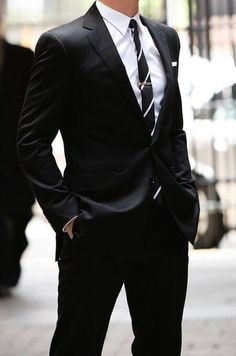 黒スーツにレジメンタルタイを合わせた着こなし