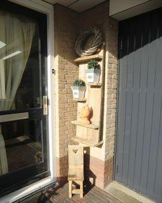 Zo kan je dus ook je min of meer standaard voordeur opleuken met een wandbord en of een stoeltje.