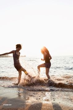Yooniq images - Women playing in waves on beach