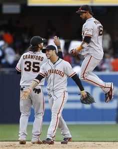 San Francisco Giants center fielder Angel Pagan jumps high while celebrating with Brandon Crawford and Gregor Blanco after the Giants 6-5 victory over the San Diego Padres in a baseball game Wednesday, June 6, 2012 in San Diego. (AP Photo/Lenny Ignelzi)