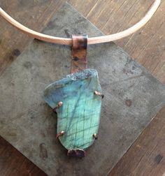 Raw and rustic this Labradorite Pendant has been left in its natural shape and polished at the front . It is set in copper and has brass arms to hold the stone in and all hands on a thick leather cord with matching rustic fittings. The leather cord measures 44cm with the fittings and